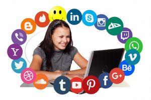 kobieta przed komputerem i ikony social media